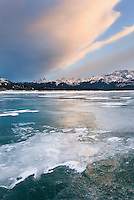 Clouds glowing in a winter sunset over the wind polished ice of Abraham Lake, Alberta Canada