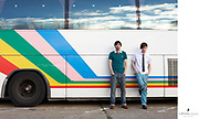 Two young men leaning against the side of a bus.