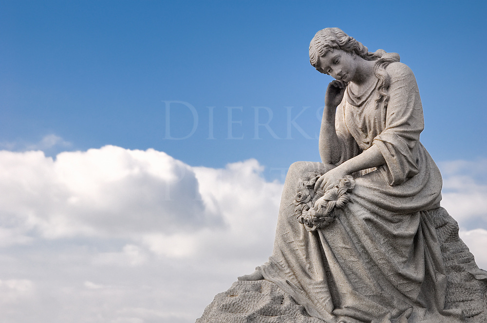 Seated mourning woman sculpted in granite against clouds and blue sky.