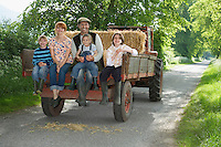 Parents with three children (5-9) sitting on trailer on country lane portrait