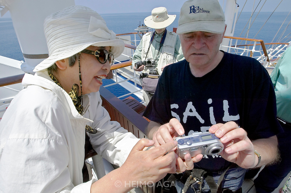 A day at sea aboard the Royal Clipper. Captain Klaus climbing to the top of the fock mast and taking souvenir photos for Japanese painter Kuriko Shigeta.