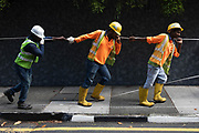 Workmen pull cable from a manhole in Somerset, Singapore.