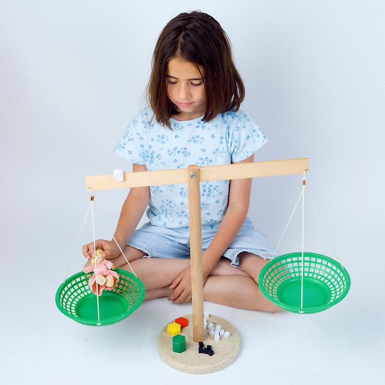Measurment using pan balance series.  Girl weighing objects using a pan balance.