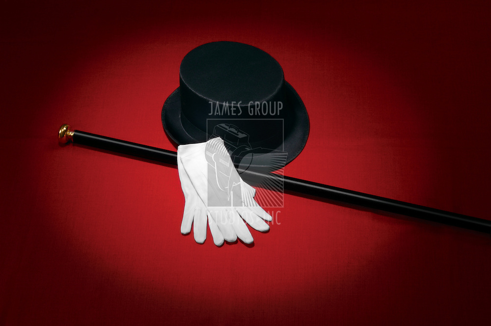 Top hat, white gloves and black cane on red background under a spotlight