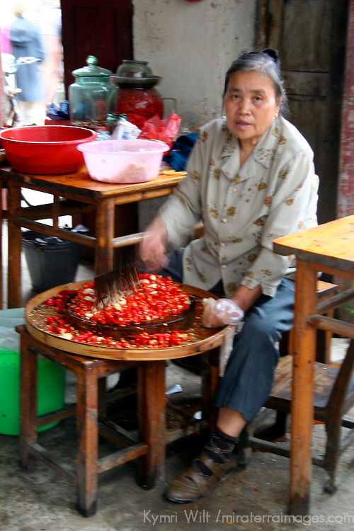 Asia, China, Guangxi, Daxu. In the kitchen of her home in Daxu, a woman prepares peppers and garlic for selling.