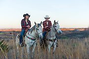 Kaylee Lowe and Clay Davis ride their horses at sunrise on the Packsaddle Wildlife Management area south of Arnett, Oklahoma.