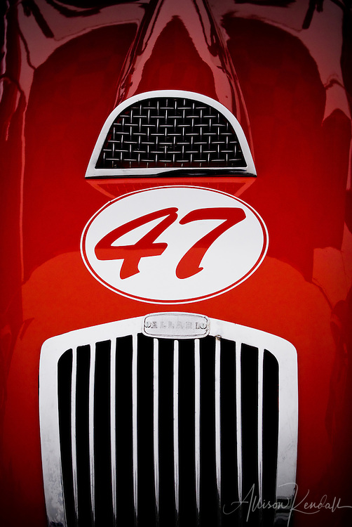 Close-up abstract view of a classic vintage race car, shiny red and chrome grill of a rare Allard automobile