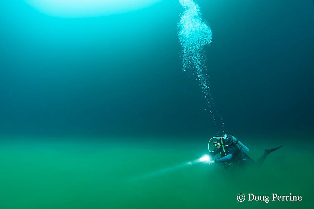 scuba diver swims along foggy boundary layer of hydrogen sulfide river that blankets the halocline at 30m depth in  Cenote Angelita, near Tulum, Yucatan Peninsula, Mexico