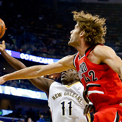 Dec 30, 2013; New Orleans, LA, USA; New Orleans Pelicans point guard Jrue Holiday (11) shoots over Portland Trail Blazers center Robin Lopez (42) during the first quarter of a game at the New Orleans Arena. Mandatory Credit: Derick E. Hingle-USA TODAY Sports