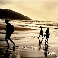 An adult and two children on the beach at sunset