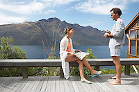 Couple in pajamas on balcony overlooking a mountain lake