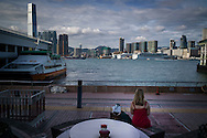 Woman in a red dress sits on a bench overlooking Hong Kong harbor and skyline, China, Asia