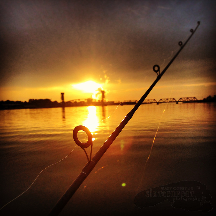 Gary Cosby Jr.  iPhone photographs  A fishing pole points to the sunset over the Tennessee River.