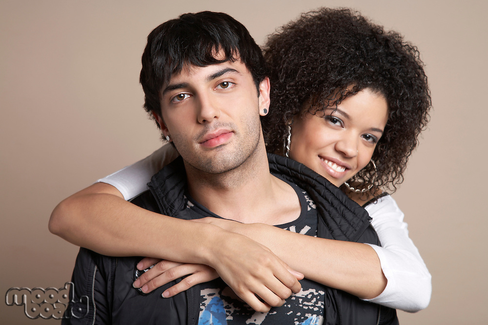 Young couple woman embracing man from behind portrait
