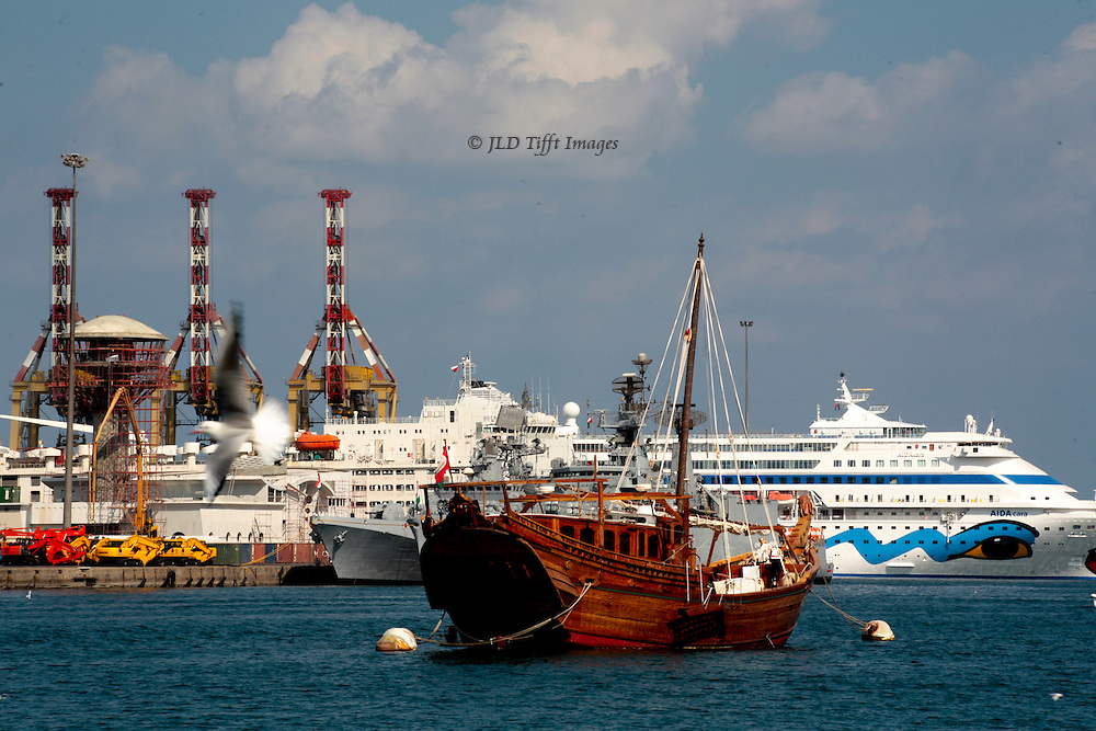 Mattrah, Muscat.  Harbor view with freighters, cruise ships, ferries, and an anchored replica of a traditional dhow.