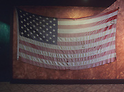 Tattered and fadded American flag hangs at Rhawn Street Studios in Philadelphia, Pennsylvania
