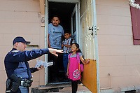 Salinas police officer Richard Lopez talks to a Fremont Street family about the CASP community policing program, and how they might best make use of the resources the Center offers.