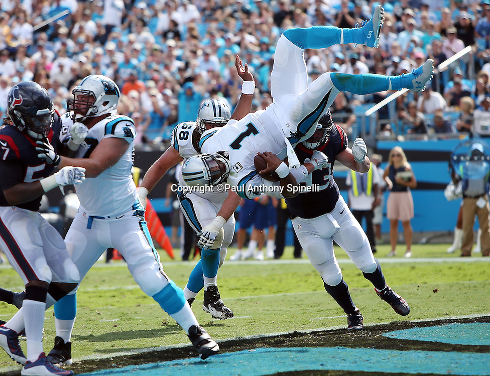 Carolina Panthers quarterback Cam Newton (1) gets hit in the back by Houston Texans defensive end Jared Crick (93) as he flies head over heels into the end zone on a 2 yard touchdown run good for a 17-10 third quarter lead during the 2015 NFL week 2 regular season football game against the Houston Texans on Sunday, Sept. 20, 2015 in Charlotte, N.C. The Panthers won the game 24-17. (©Paul Anthony Spinelli)