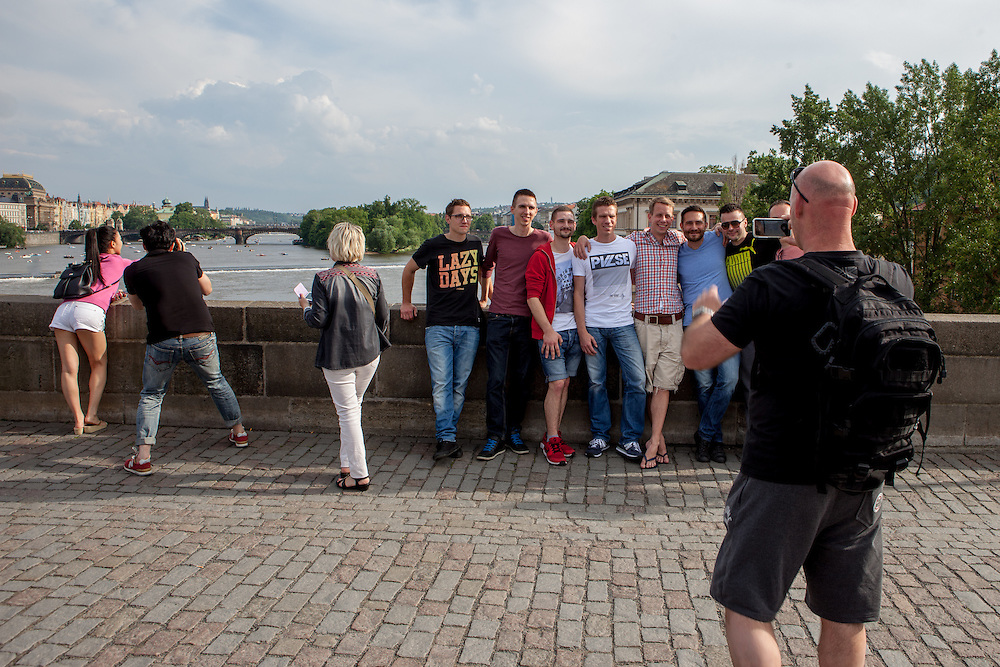 A group of German tourist getting photographed  on Charles Bridge in Prague. The Charles Bridge (Czech: Karlův most) is a famous historic bridge that crosses the Vltava river in Prague, Czech Republic and is probably the Nr.1 tourists magnet in the city.