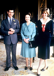 Queen Elizabeth II poses for photographs with the Prince of Wales and his fiancee, Lady Diana Spencer at Buckingham Palace, after a Privy Council Meeting.