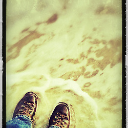 """Boots in the water on the beach at New Castle Common, New Castle, New Hampshire. iPhone photo - suitable for print reproduction up o 8"""" x 12""""."""