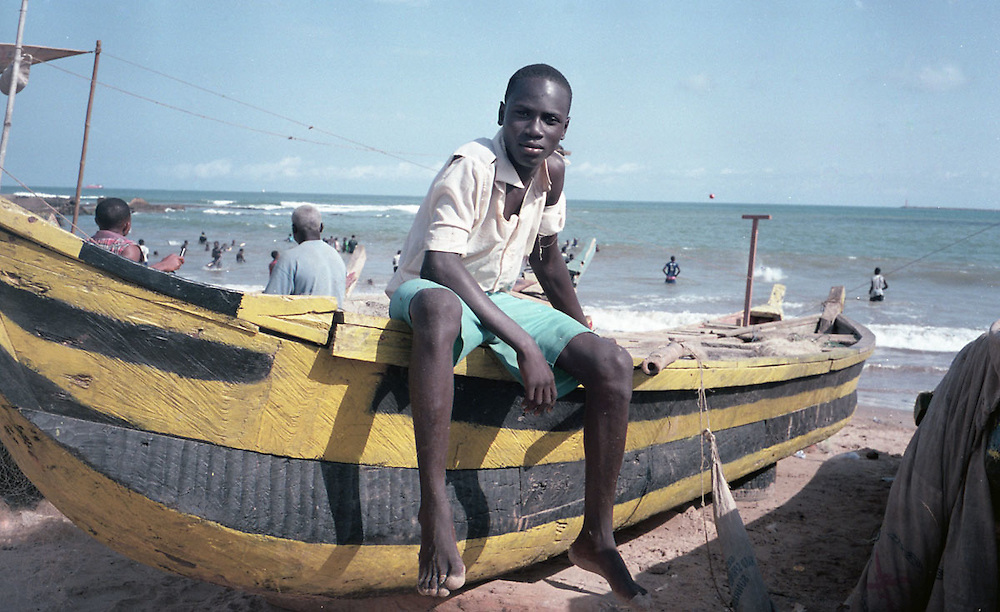Kid sitting on a fishing boat at the beach on New Takoradi, Ghana 2011
