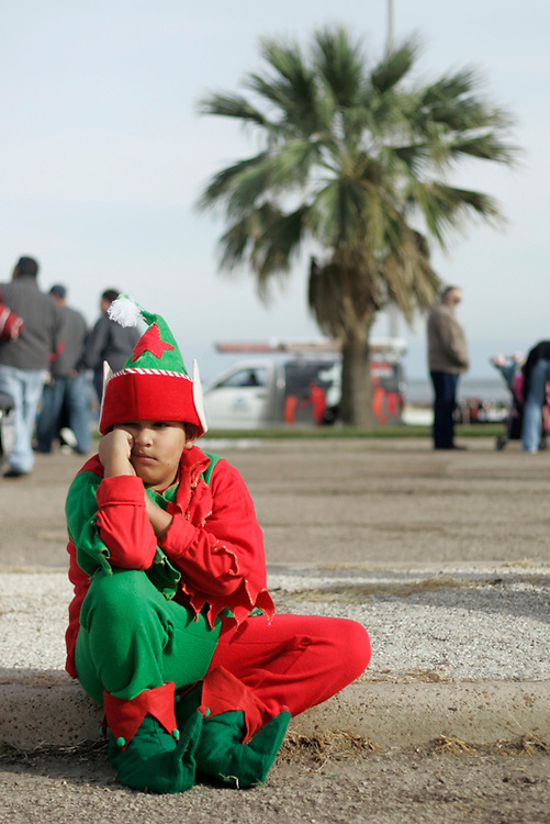 Michael Zamora/Caller-Times.Zach Garcia, 9, a student at Ella Barnes Elementary, sits on the curb in his elf costume Saturday, Dec. 5, 2009 waiting for the start of the EOG Resources Children's Parade in Corpus Christi. Garcia said he has participated in the parade the last two years.