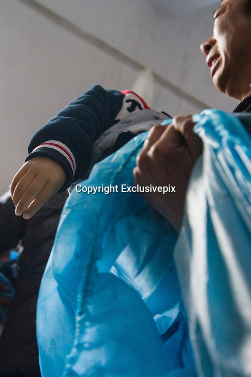 PENGLAI, CHINA - NOVEMBER 19: (CHINA OUT) <br /> <br /> 11 Children Killed In School Bus Accident In East China<br /> <br /> A relative of child victim holds his child at Penglai Funeral Parlour on November 19, 2014 in Penglai, Shandong Province of China. 11 kindergarten children and 1 driver died and 3 kindergarten children were injured during a collision between a truck and a minibus on the slip road to the new Yantai airport in Chaoshui Town, Penglai City of East China\'s Shandong Province. The minibus belonged to a local private kindergarten and was overloaded at that time according to Xinhua\'s report. The cause of the traffic is still under investigation. ©Exclusivepix