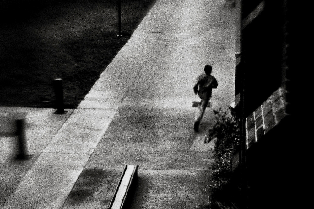 Creative black and white image of a teen running to class at his prep school in Asheville, North Carolina.