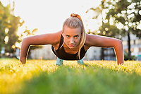 Portrait of young attractive woman planking in park with lens flare