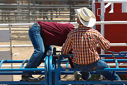 cowboy with his head in another cowboy's lap on a ranch