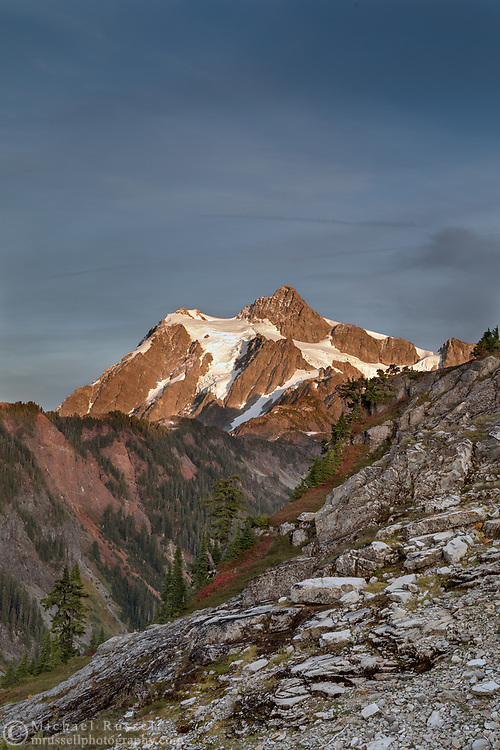 Sunset shines on Mount Shuksan from the Artist Point to Huntoon Point trail along Kulshan Ridge in Washington State's North Cascades Range. Photographed from Kulshan Ridge in the Mount Baker-Snoqualmie National Forest though Mount Shuksan itself lies in North Cascades National Park.