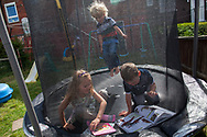 McKenzie (6), Lucas (5), Regan (5), read in their trampoline at home in Shefield UK Tuesday, Aug. 12, 2014The D'Arby family is involved in the FAST  (Families and Schools Together) program which encourages parents to read to their children at home.(Elizabeth Dalziel for Save the Children )