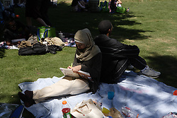Stock photo of a man and woman relaxing on a picnic blanket in the shade