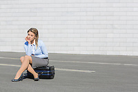Tired businesswoman sitting on luggage