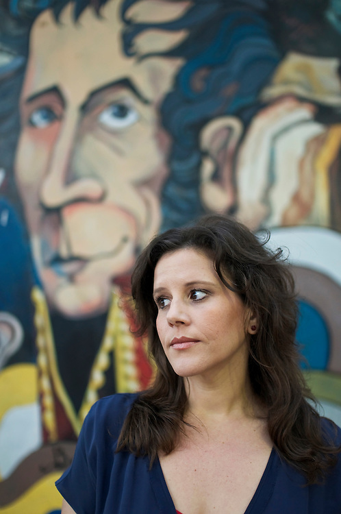 """Venezuelan-American Eva Golinger, poses for a portrait by a painting of revolutionary hero, Simon Bolivar in Caracas, Venezuela. Golinger is an outspoken supporter of Venezuelan President, Hugo Chávez, who she said refers to her as, La novia de Venezuela (""""The Sweetheart of Venezuela""""). Golinger is an attorney, book author and regularly published writer. She passionately defends Chávez, his socialist policies and his Bolivarian revolution in much of her work, and says it is unfortunate that the American mainstream media portrays him as a tyrant dictator."""