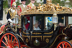 © London News Pictures. 09/05/2012. London, UK.  Queen Elizabeth II being driven down The Mall in a horse drawn carriage to attend the State Opening of Parliament on May 09, 2012 in London. In a speech to Members of Parliament and Peers in The House of Lords, Queen Elizabeth II will officially open a new session of parliament, which will set out the government's agenda and legislation for the coming year. Photo credit: Ben Cawthra/LNP