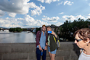 "A couple is doing a ""selfie"" with a smart phone on Charles Bridge. The Charles Bridge (Czech: Karlův most) is a famous historic bridge that crosses the Vltava river in Prague, Czech Republic and is probably the Nr.1 tourists magnet in the city."