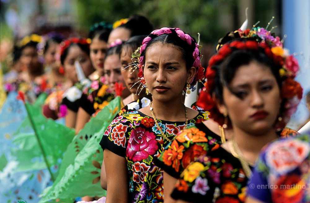 "Juchitàn, Velas (traditional celebrations) of Ixtepec.  ""Regada de Frutas"", a procession along village's streets. The tehuanas are the archetype of an ancient and legendary Mexico, told in the murales of Diego Rivera and impersonated also by Frida Kalho that often wore these traditional dresses. But these showy dresses, and the rich golden ornaments that accompany them, are above all an instrument of auto-representatiom for these active women which the control of the local markets confers an independent economic power that is reflected in the self confidence. Even in the development of the festivities, where the women often dance a lot among them while the men remain seated watching."