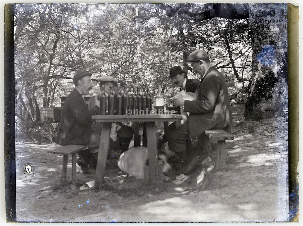 a picnic outdoors with many wine bottles on the table 1900s France