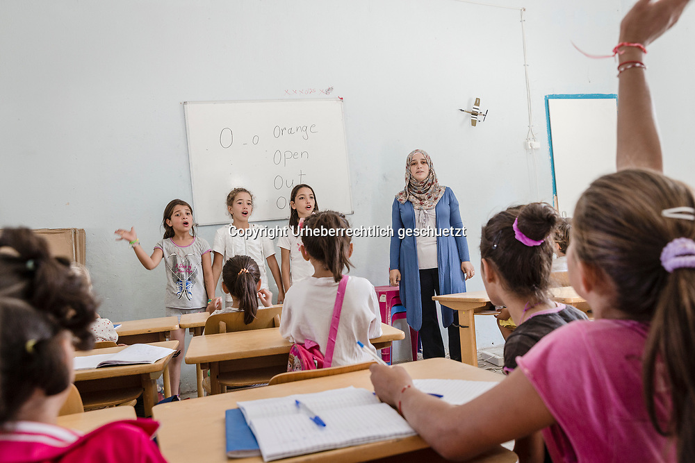 Greece, Lagkadikia, Tahany ALKAMELL, age 40, from Idlip, Syria, turned back to her profession as a english teacher. She teaches  for two hours several times a week a group of 29 children, including her own daugther Dania, age 9. Second from left, standing infront of the classmates. Her two sons Bakir, age 20 and Abdullah, age 16, are in Germany. Booth are accepted as refugees seeking asylum in Germany.