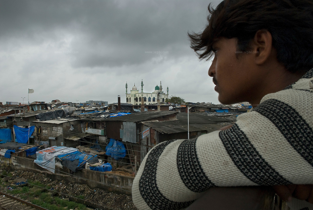 A young man catching a cool breaze on the railroad bridge overlooking Dharavi's main mosque. About a third of the slum's population is Muslims.