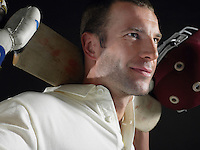 Cricket player holding cricket bat behind shoulders close-up