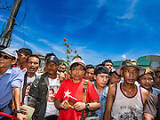 23 JUNE 2016 - MAHACHAI, SAMUT SAKHON, THAILAND: Burmese migrant workers wait for Aung San Kyii to arrive in Samut Sakhon, a province south of Bangkok. Tens of thousands of Burmese migrant workers, most employed in the Thai fishing industry, live in Samut Sakhon. Aung San Suu Kyi, the Foreign Minister and State Counsellor for the government of Myanmar (a role similar to that of Prime Minister or a head of government), is on a state visit to Thailand. Even though she and her party won the 2015 elections by a landslide, she is constitutionally prohibited from becoming the President due to a clause in the constitution as her late husband and children are foreign citizens        PHOTO BY JACK KURTZ