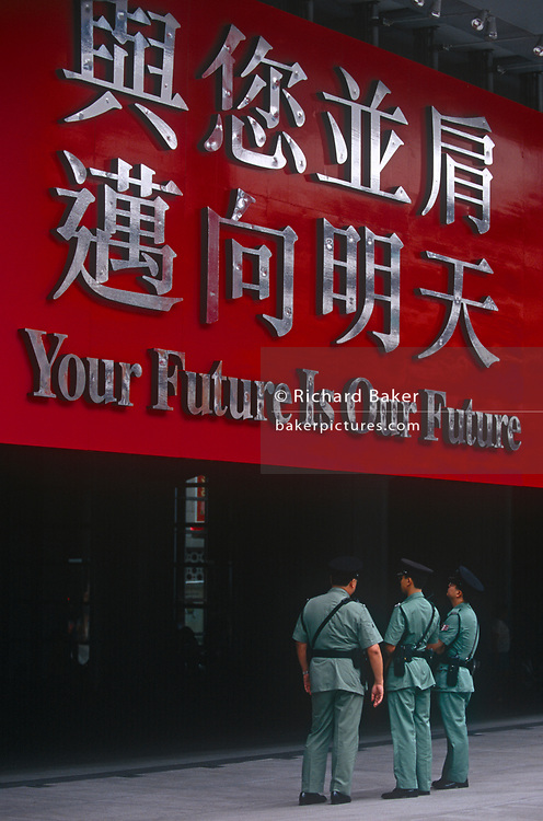 Police officers look at the large corporate banners about the future of Hong Kong hang over the entrance of the HSBC bank in Central, the day after the Handover of sovereignty from Britain to China, on 30th June 1997, in Hong Kong, China. Midnight signified the end of British rule, and the transfer of legal and financial authority back to China. Hong Kong was once known as 'fragrant harbour' (or Heung Keung) because of the smell of transported sandal wood.