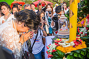 06 JANUARY 2013 - BANGKOK, THAILAND: A woman prays in front of a relic of the Buddha's hair during a service for the relic in Bangkok. The relic has been on display in Bangkok for about 10 years. There was a ceremony in Sanam Luang in Bangkok Sunday to honor the relic. People prayed for it and received blessings from Buddhist monks and Brahmin priests who presided over the service. The hair is being moved to Ayutthaya, where it will be displayed in a Buddhist temple. The piece of hair has been on loan to Thai Buddhists from a Buddhist temple in Sri Lanka.    PHOTO BY JACK KURTZ