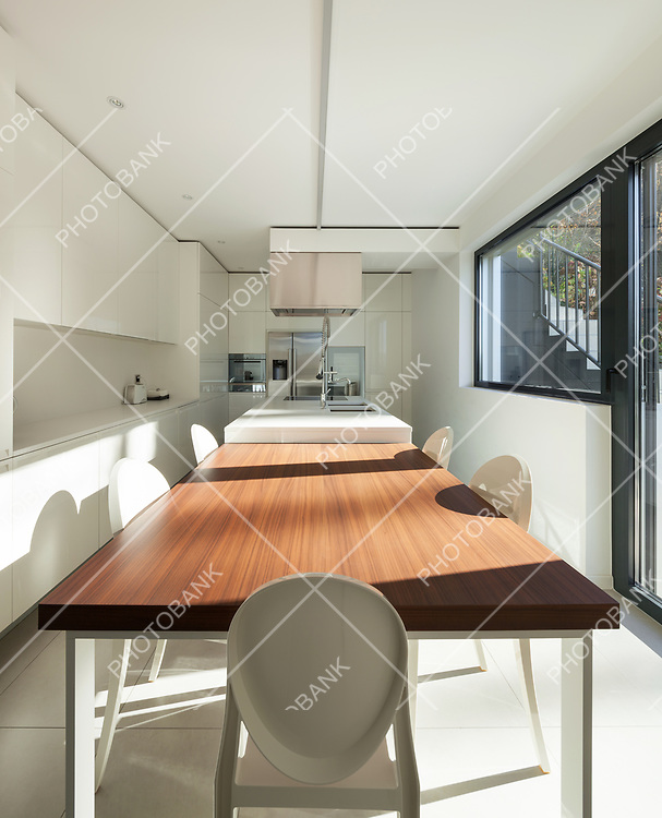 Interior of a modern apartment, dining table in domestic kitchen, perspective view