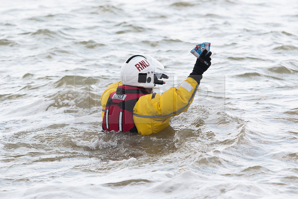 © Licensed to London News Pictures. 15/05/2016. Brighton, UK. A member of the Brighton RNLI lifeboat crew carries ice creams for his colleagues who are patrolling the sea off Brighton. Photo credit: Hugo Michiels/LNP