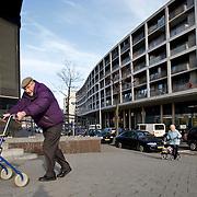 Nederland Rotterdam 14 maart 2008 20080314.Zelfstandige ouderen. Ouderen lopen met rollator met daarin boodschappen een heuveltje op in achterstandswijk Afrikaanderbuurt in Rotterdam zuid..Zelfstandige ouderen besparen de samenleving veel geld.Ouderen die thuis blijven wonen en daar de nodige zorg, hulp, hulpmiddelen en aanpassingen krijgen, zijn over het algemeen gelukkiger dan ouderen die in een instelling (verzorgingshuis of verpleeghuis) gaan wonen. Bovendien besparen ze samenleving veel geld. Dat blijkt uit een onderzoek door het Sociaal Cultureel Planbureau (SCP), in opdracht van het College voor Zorgverzekeringen..Steeds meer ouderen blijven zelfstandig wonen, zo blijkt uit de cijfers van het SCP. Tussen 1998 en 2002 is het aantal bewoners van verzorgingshuizen en verpleeghuizen met 6% gedaald, terwijl er door de vergrijzing steeds meer ouderen bijkomen..Doordat meer ouderen thuis wonen, nemen de kosten voor hulp thuis toe. Steeds meer ouderen vragen individuele huursubsidie, gemeentelijke voorzieningen (zoals woningaanpassingen, vervoersvoorzieningen en scootmobielen), zorg, hulp en begeleiding (via de thuiszorg of met een persoonsgebonden budget), alarmering, maaltijdservice, enzovoorts..Het lijkt dan net alsof de kosten voor al die voorzieningen enorm de pan uit rijzen. Maar dat is niet zo, heeft het SCP berekend. Ouderen die thuis blijven wonen besparen de samenleving juist geld. Die besparing bedraagt kan oplopen tot EUR 16.000 per persoon per jaar. Ook ouderen met ernstige beperkingen die intensieve zorg nodig hebben, zijn thuis vaak goedkoper uit dan in een instelling. Geld uitgeven aan goede zorg en voorzieningen zodat mensen langer zelfstandig kunnen blijven wonen, levert blijkbaar uiteindelijk geld op. 'Per saldo zullen de kosten van de gezondheidszorg dalen als meer ouderen thuis blijven wonen,' schrijft het SCP...Foto David Rozing