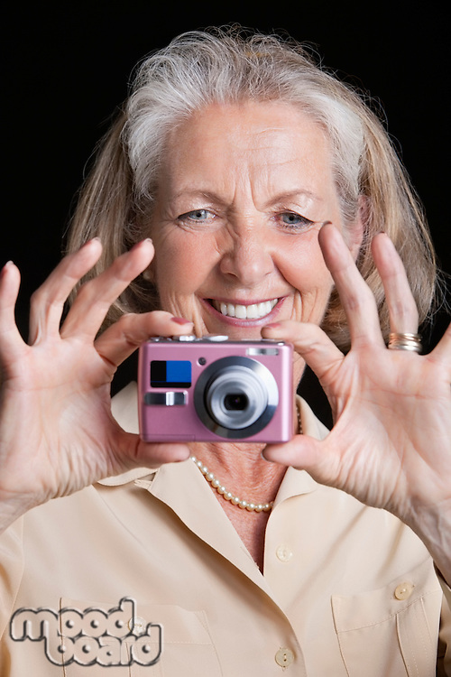 Smiling senior woman taking picture with camera against black background